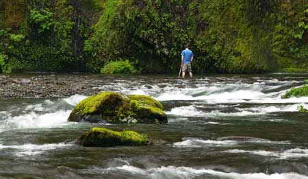 "Photographer standing in Eagle Creek for the ""classic"" shot of Punch Bowl Falls"