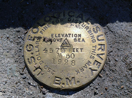 The original USGS survey marker at the east end of the bridge has been uncovered from years of debris