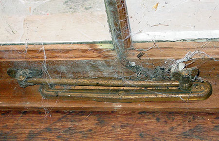 Original brass window hardware was still present in 2008, but has since been stripped from by building by vandals