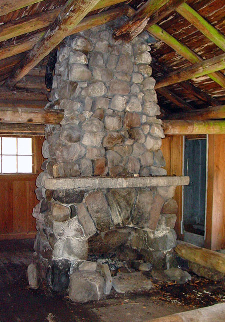 This magnificent fireplace stands at the center of the guard station; the room in the background is a built-in shower, lined with galvanized steel.