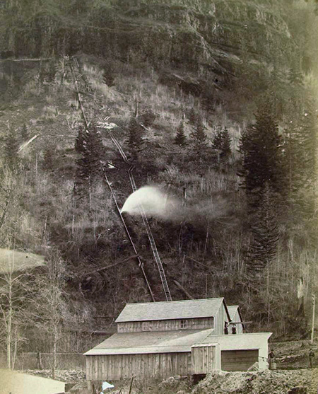 This 1890s photo shows water spouting from the long penstock that drove Myron Kelly's pulp mill