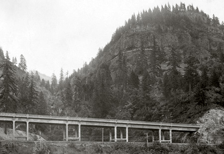 Completed McCord Creek bridge in 1915, with the Kelly pulp mill conduits visible in the cliffs high above, and Elowah Falls behind the bridge