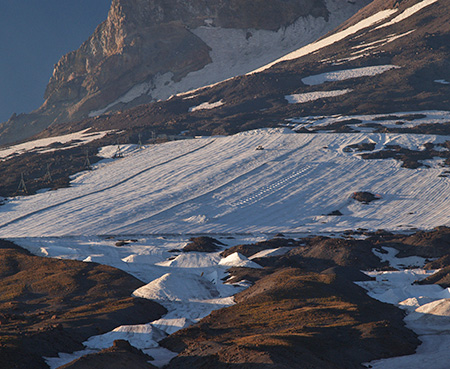 Like tractors on a corn field, snowcats plow (and salt) the Palmer Glacier for summer skiers